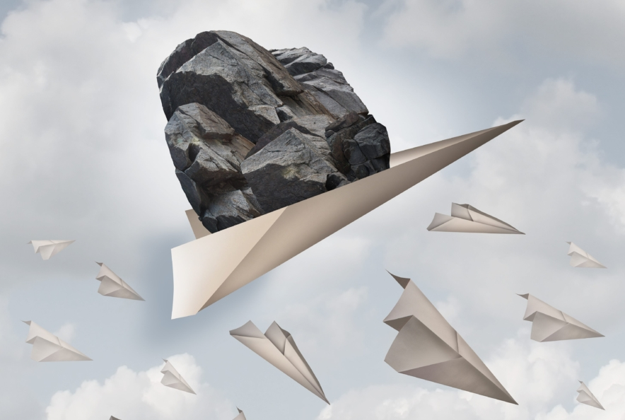 Power of motivation business success concept as a paper plane hauling a heavy rock with a group of failing origami airplanes as a metaphor for the force of determination.