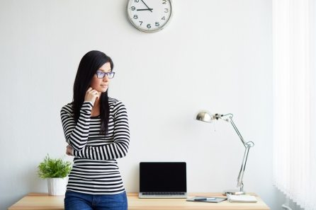 Young woman stands in the home office and looks out the window